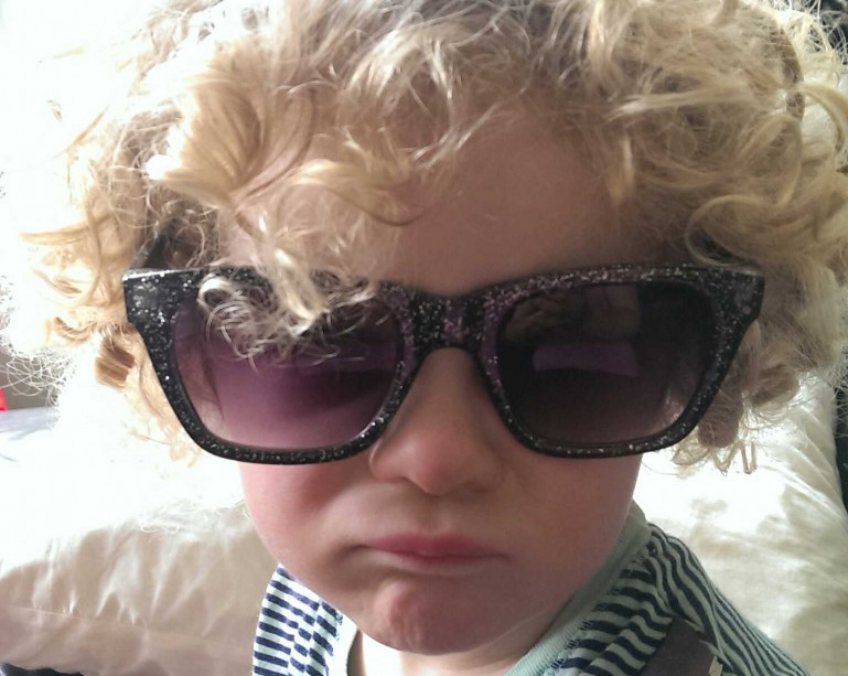Child in sunglasses with a pout
