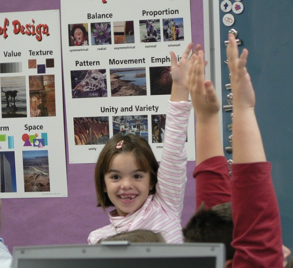child with hand up in classroom